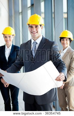 young construction manager holding blue print in front of colleagues
