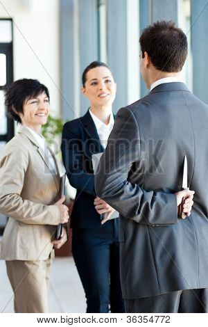 dangerous businessman hiding knife behind his back while handshaking with businesswoman