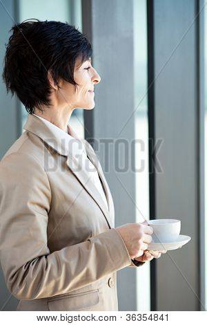 elegant middle aged businesswoman drinking coffee in office
