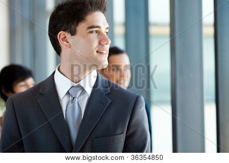 young businessman looking outside office window