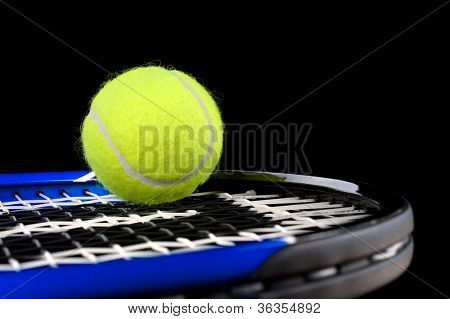 A new green tennis ball resting atop a blue racquet with a black background.