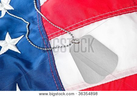 A pair of blank dog tags on an American flag.  Tags are blank for placement of copy.