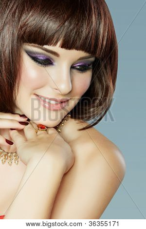 portrait of a beautiful young smiling woman with short brown hair and smoky eyeliner eye makeup, wearing dark manicure