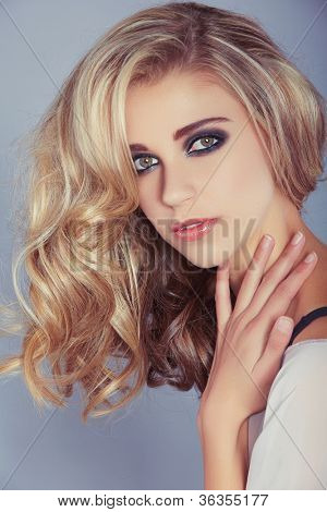 beautiful blond girl with curly long hair and smoky eyeshadow makeup