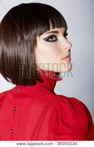 beautiful young woman with short brown hair in red vintage blouse wearing smoky purple eyeshadow and dramatic eyeliner.