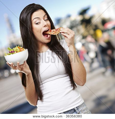 woman choosing a slice of pizza instead of a salad against a street background