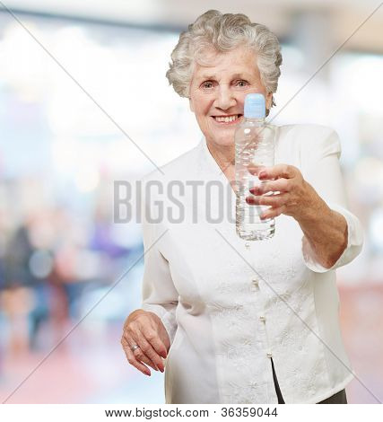 portrait of healthy senior woman holding a water bottle indoor