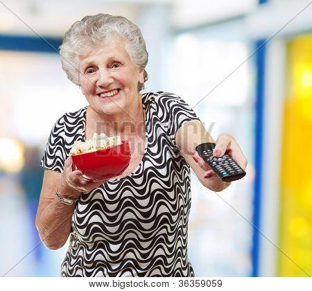 portrait of happy senior woman looking the tv indoor