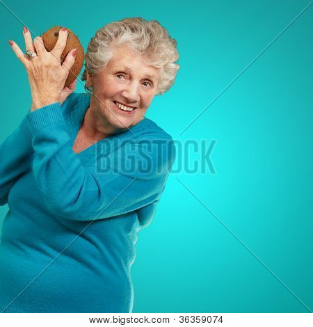 Senior happy woman holding coconut isolated on blue background