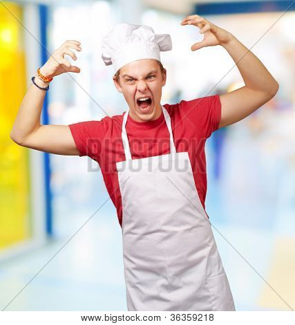 portrait of young cook man wearing apron doing aggressive gesture indoor