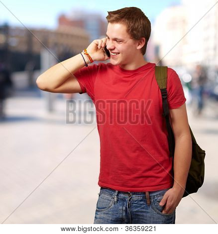 portrait of young man talking on mobile at street