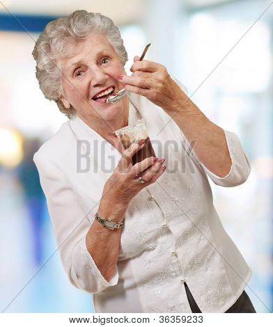 portrait of senior woman eating chocolate and cream cup indoor