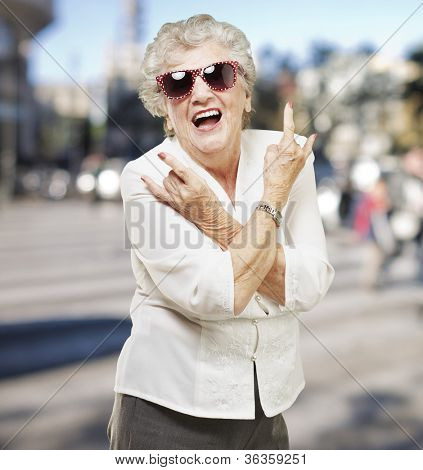 portrait of senior woman doing rock symbol at city background