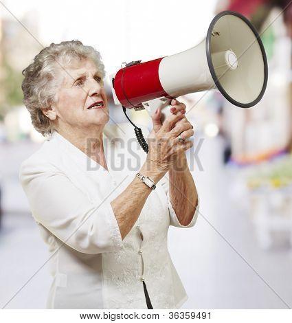 portrait of senior woman holding megaphone at city