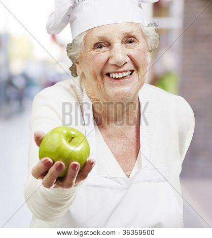 cozinheiro sênior mulher oferecendo uma maçã verde contra um fundo de rua