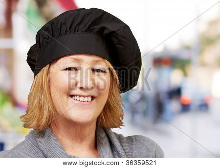 portrait of middle aged cook woman smiling at street
