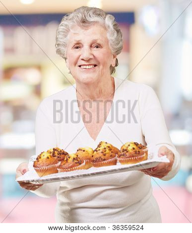 portrait of senior woman showing a chocolate muffin tray indoor