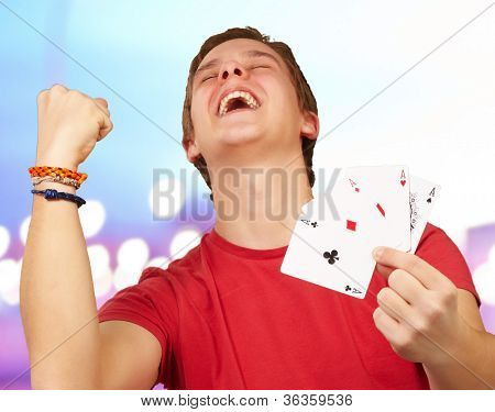 portrait of young man doing a winner gesture playing poker over abstract background