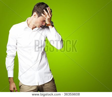 Angry young man doing frustration gesture over green background