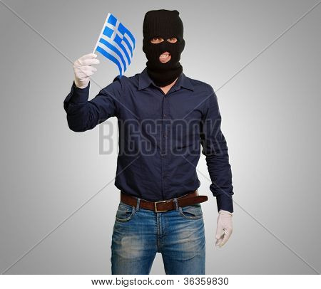 Man wearing robber mask and holding flag on grey background