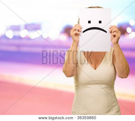 mature woman holding sad smiley, outdoor