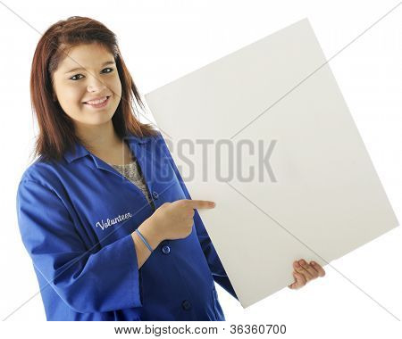 A pretty young volunteer happily pointing to a sign left blank for your text.  On a white background.