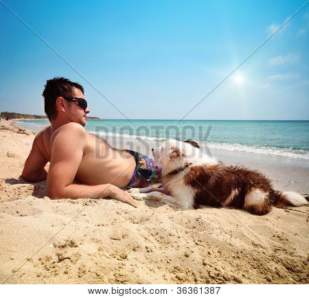 men with dog on a beach