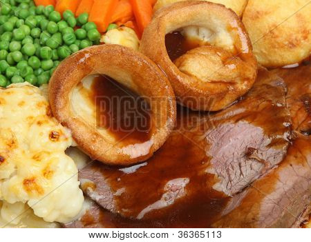 Traditional Sunday roast beef dinner with Yorkshire puddings and gravy.