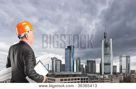 Male engineer looking at buildings in the financial centre in Frankfurt, Germany