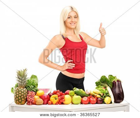 Healthy smiling woman with fruits and vegetables giving a thumb up isolated on white background