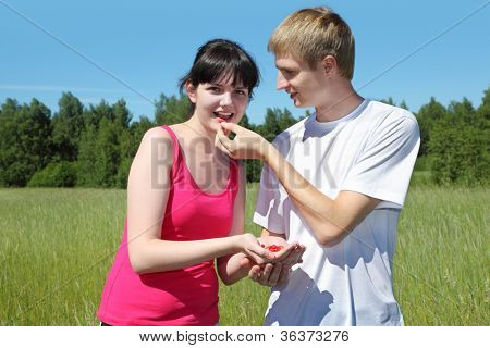 Husband feeds wife berry from hand