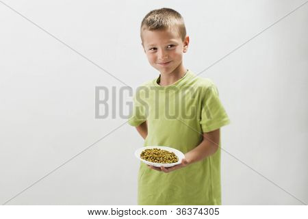 Little boy with peas, making negative facial expression