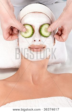 Natural beauty treatment with facial mask and cucumber.