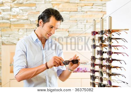 Young man at optician with glasses, he might be customer or salesperson and is looking for sunglasses