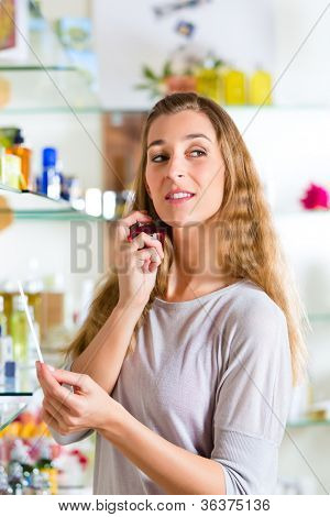 Young woman buying perfume in a shop or store, testing the fragrance with a paper tester and on the neck