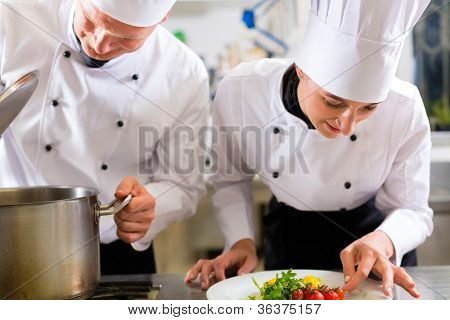 Two chefs - man and woman - in hotel or restaurant kitchen working and cooking in team