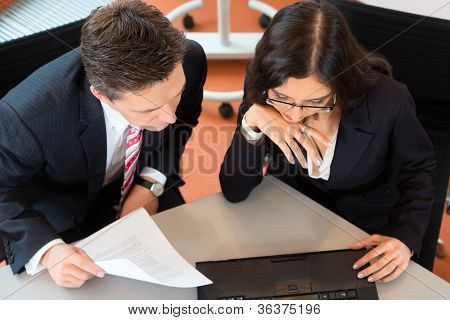 Businesspeople sitting at office desk with a document and laptop