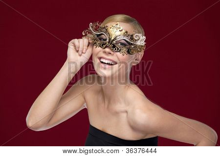 Young woman with patterned masquerade mask, isolated on purple