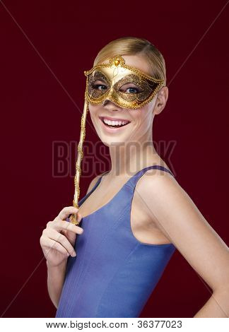 Young woman with masquerade mask, isolated on purple