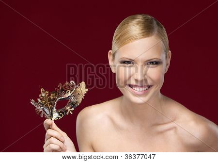 Pretty lady with patterned masquerade mask, isolated on purple