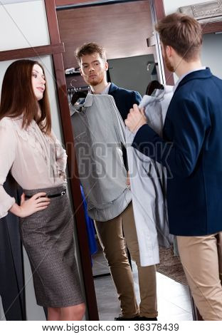 Young man consults with girlfriend while selecting a spruce shirt