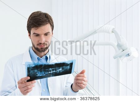 Dentist carefully examines the roentgenogram, white background.