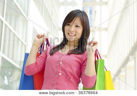 Feliz shopper asiático jovens segurando o saco de compras em shopping