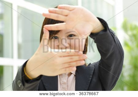 Smiling Asian business woman making a frame with fingers
