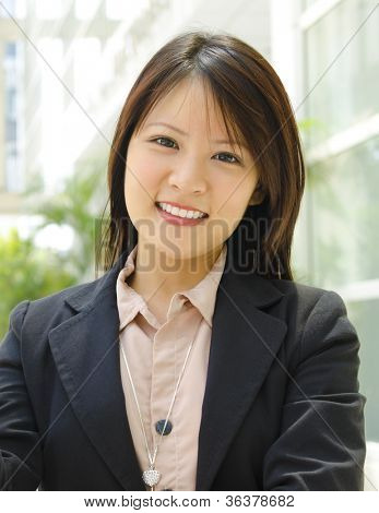 Young Asian executive standing outside office building