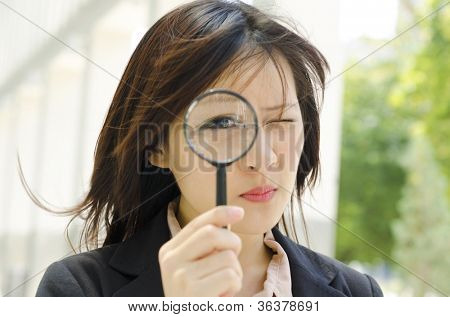 Asian business woman with magnifying glass to the eye
