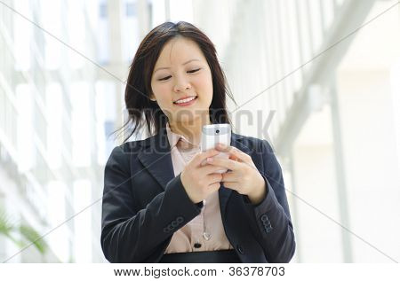 Happy oriental Asian young executive using mobile phone to online / texting / sms