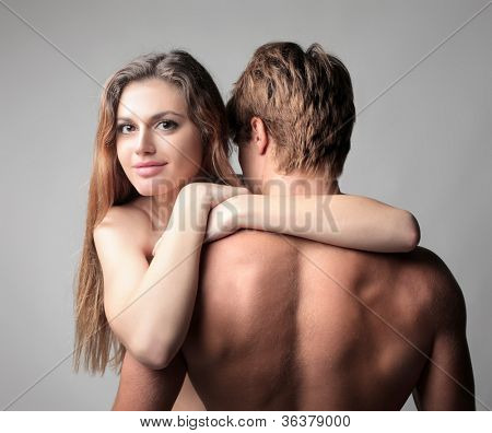 Smiling beautiful young woman embraced to her boyfriend