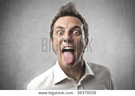 Funny young man sticking out his tongue