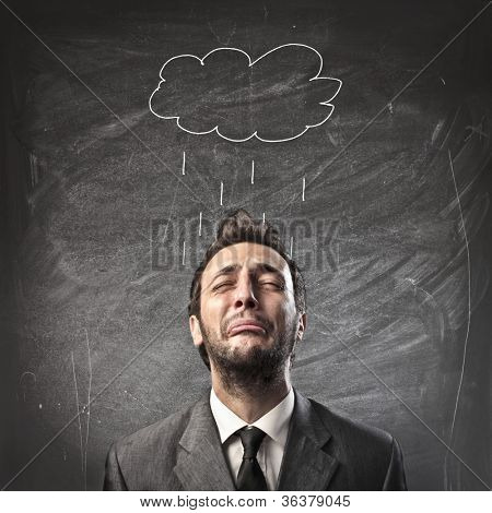 Sad young businessman with raincloud over his head